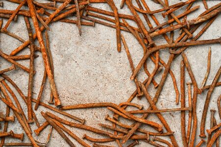 Rusty used nails on a cement metal background Stock Photo