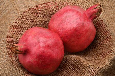 Ripe seasonal pomegranates on burlap background Stock Photo