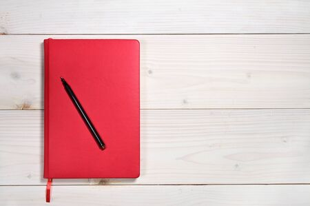 Red notebook for everyday notes on a white wooden background