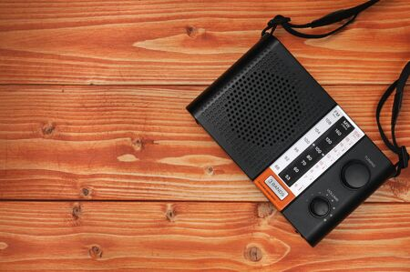 Vintage radio for listening to radio programs on a wooden background