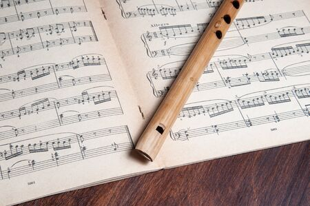 Vintage bamboo flute on the background of vintage musical notes 写真素材