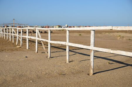Wooden fence in the sand on an abandoned summer beach