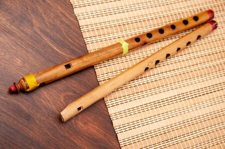Vintage bamboo fife and flute lie on a straw mat