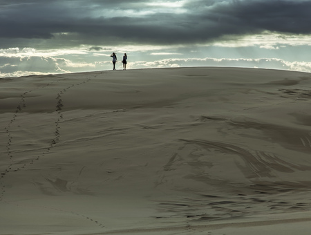 Girl friends at the hill of sand dune Editorial