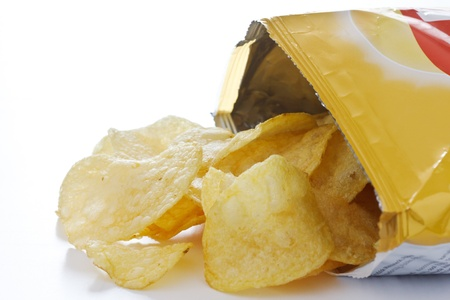 potato crisps: Potato crisp packet opened with crisps spilling out Stock Photo