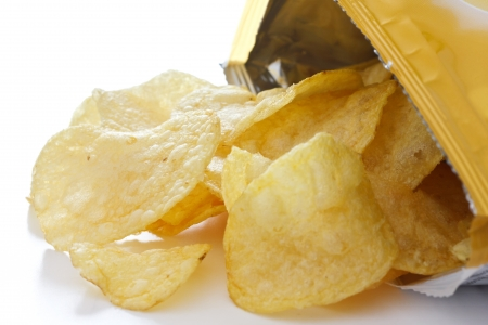 Potato crisp packet opened with crisps spilling out photo