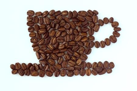 semilla de cafe: Caf� tostado en grano tumb�bamos en la forma de una taza y el plato en una superficie blanca