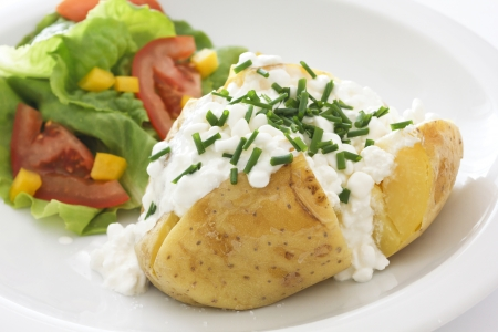baked potato with cottage cheese, chives and fresh salad on a white plate photo