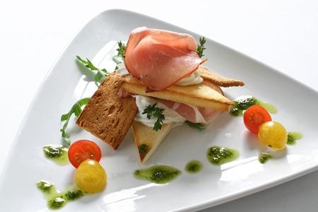 melba: Aperitivo con el jamón, tostadas Melba y tomatitos Foto de archivo