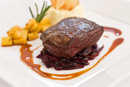 red braised: A big piece of baked fillet steak sitting over red braised cabbage on a white plate with light background