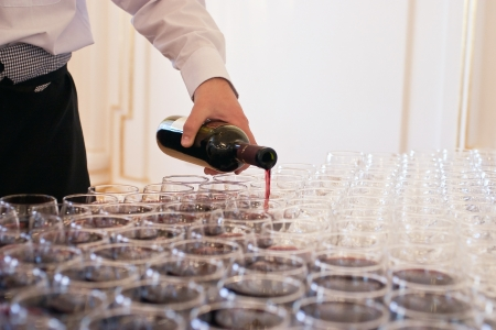 Waiter pouring red wine into many glasses photo