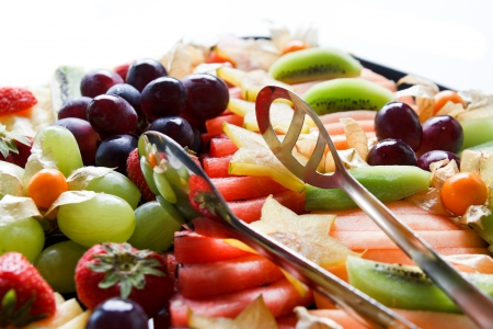 Mixed fruit platter with tongs in sunlight
