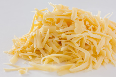 Grated yellow cheese on white photo