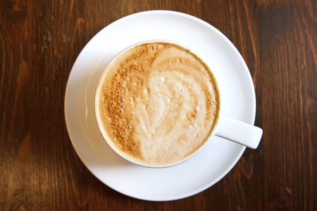 Classic foamy cappuccino in on a dark grained wood table. Detail. From above. Stockfoto
