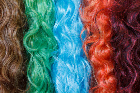 Coloured wigs with long wavy fake hair hanging next to each other. photo