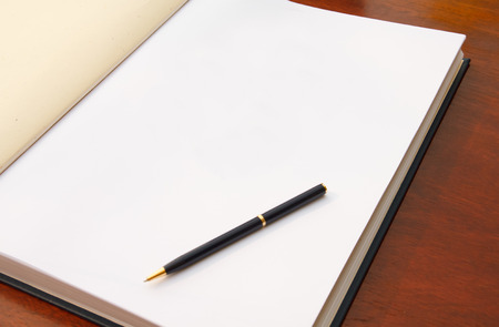 Large open book on wood table with white blank page and pen. Ready for your text.