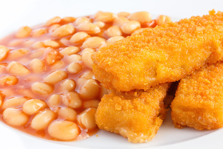 Plate of baked beans with fried fishfingers. photo