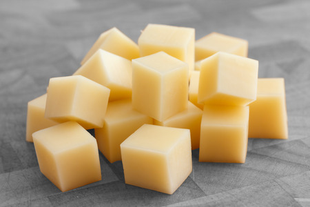 Cubes of yellow cheese stacked randomly on wood chopping board. Stockfoto
