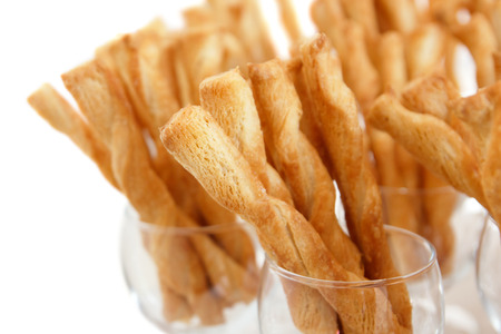 twists: Many cheese pastry twists in wine glasses and white background
