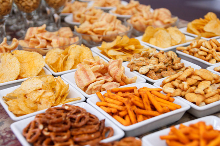 Many types of savoury snack in white dishes