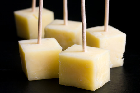 cubed: Cubes of yellow cheese on toothpicks. Black background.