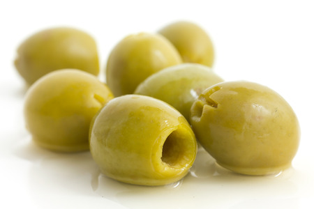 pitted: Pitted green olives with brine on white. Stock Photo