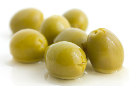 brine: Pitted green olives with brine on white. Stock Photo