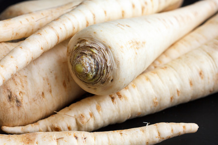 parsnip: Whole parsnip roots on black surface.