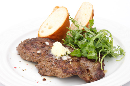 Perfect roast pork rib eye steak with baguette and simple salad topped with melting butter.