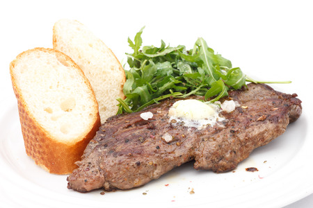 Perfect roast pork rib eye steak with baguette and simple salad topped with melting butter. photo