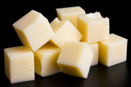 Yellow cheese cubes on black surface.