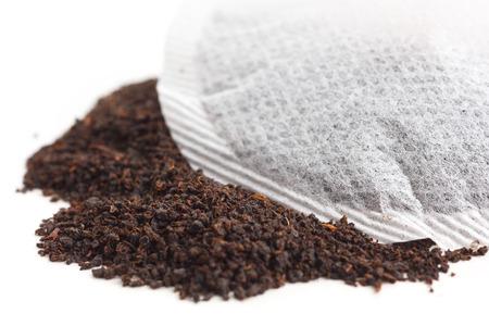 Round teabag on tea leaves on white surface. photo