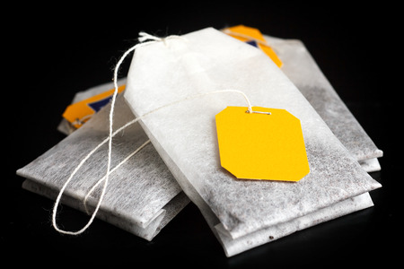 tagged: Tagged teabags with string on black surface. Stock Photo