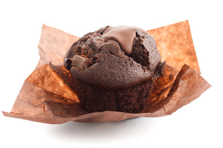 unwrapped: Chocolate chip muffin in brown wax paper. Unwrapped. Stock Photo