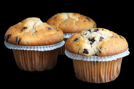 Three light chocolate chip muffins in wax liner on black.
