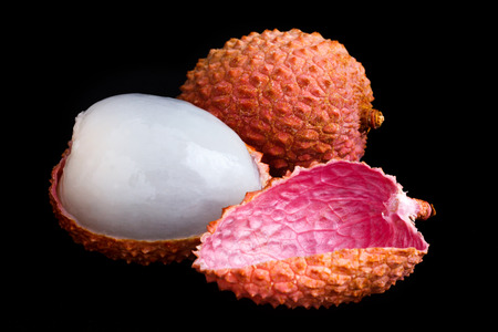 removed: Single litchi with skin removed and flesh. On black.