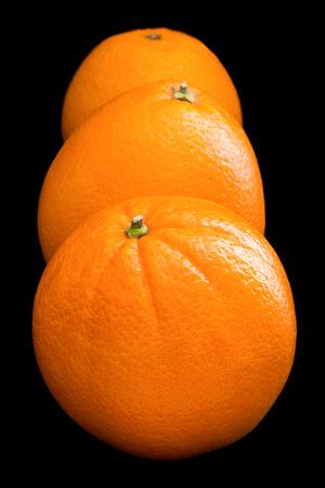 arranged: Three oranges arranged on black. Stock Photo