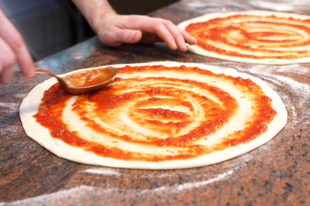 pizza base: Tomato sauce being spread on pizza base. Stock Photo