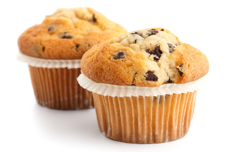 Two light chocolate chip muffins in wax liner on white. Stock Photo