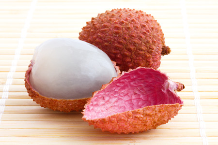 litchi: Single litchi with skin removed and flesh. On bamboo matt.
