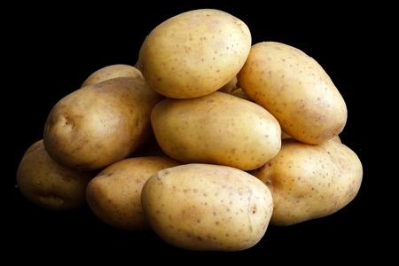 Pile of potatoes arranged on black. photo