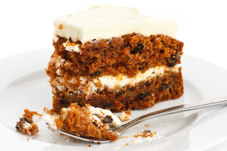 eaten: Slice of carrot cake with rich frosting. On plate. Stock Photo
