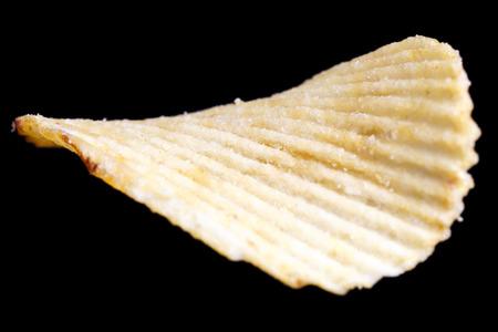 ridged: Single ridged fried potato crisp on black.