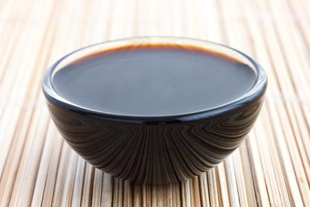 soja: Salsa Soja in piatto di vetro. Sulla stuoia di bamb�. Archivio Fotografico