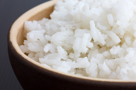 jasmine rice: Rustic bowl of cooked white rice on dark surface. Detail.