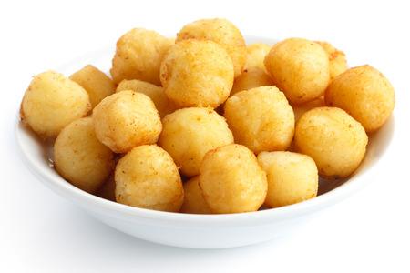 Bowl of fried small potato balls on white.