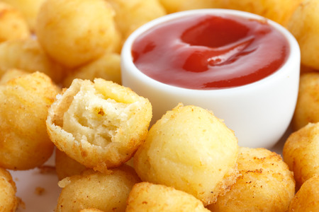 tots: Bowl of fried small potato balls with Pot of ketchup.