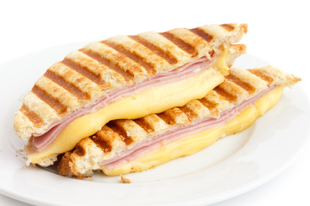 melted cheese: Toasted ham and cheese panini sandwich.