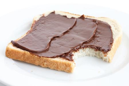 missing bite: Chocolate nut spread on sliced white bread on plate. Bite mark.