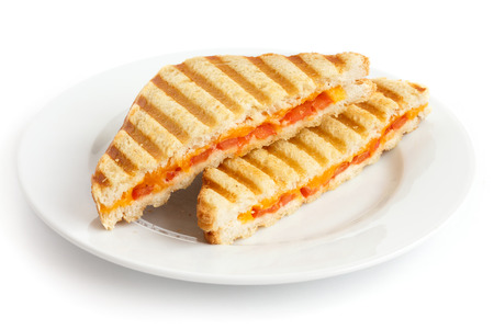 Classic tomato and cheese toasted sandwich on white plate.